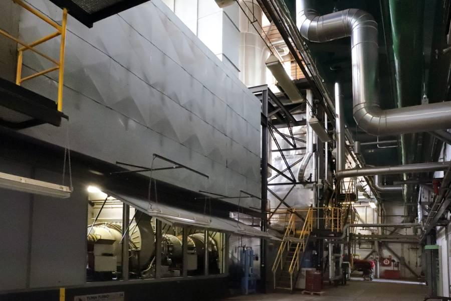 Pohľad na spaľovaciu turbínu kogeneračnej jednotky s otvorenými dverami turbosetu, v pozadí spalinový kotol kogeneračnej jednotky.