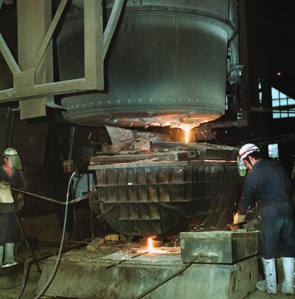 Odlievanie ocele z hlavnej panvy do medzipanvy na prvom zariadení plynulého odlievania ocele.